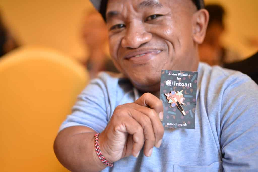 Budiarta, seniman dari Yayasan Cahaya Mutiara Ubud, sedang memegang sebuah pin hasil kolaborasi seniman Andre Williams dengan IntoArt, yaitu wirausaha sosial berbasis di Inggris